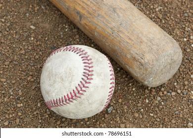 A baseball bat and ball in a baseball diamond