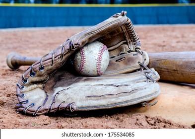 Baseball bat, glove, and ball on base on field.