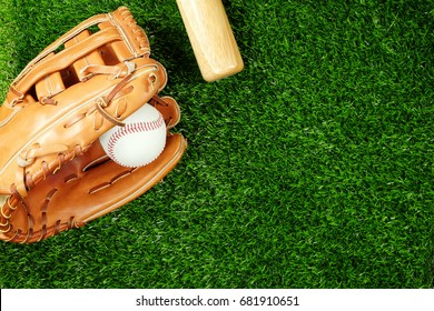 Baseball bat with glove and ball on field, top view.