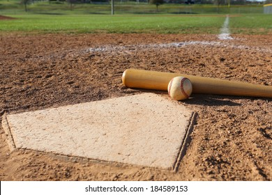 Baseball and Bat at Home Plate with the Field Beyond