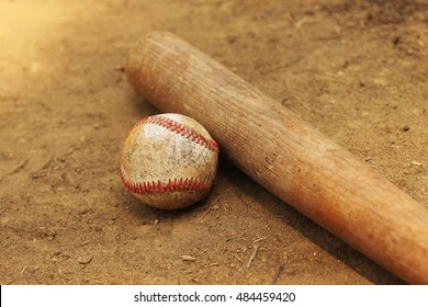 Baseball and bat on dirt