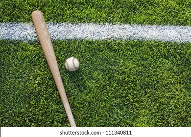 Baseball and baseball bat on grass field with white stripe viewed from above