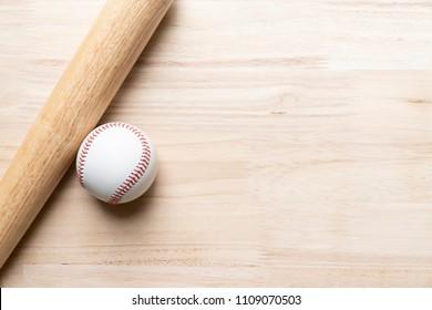 baseball and baseball bat on wooden table background, close up