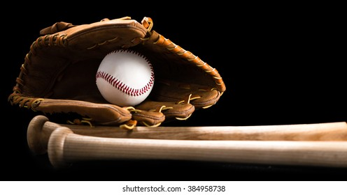 Baseball bats balls and glove isolated on black background