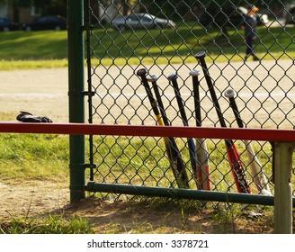 baseball bats leaning against a baseball backstop
