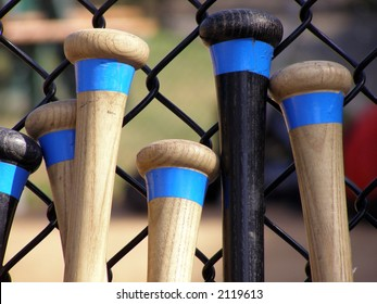 Baseball bats leaning against a batting cage fence.