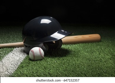 Baseball, batting helmet, and bat on field with stripe and dark background