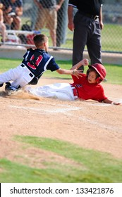 Baseball boy sliding in at home plate during game.