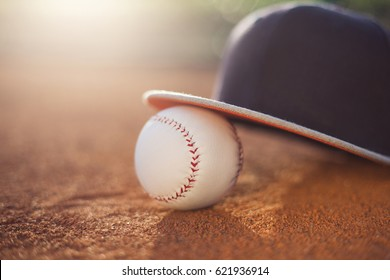 Baseball cap and baseball ball on baseball field