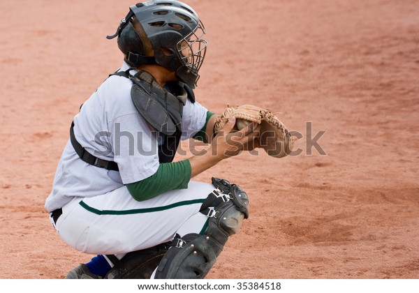 baseball catcher in position with ball in catcher's mitt