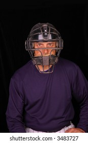 Baseball catcher wearing face mask with black background