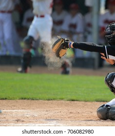 A baseball catcher's mitt explodes in dust after a pitch is caught.