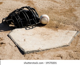 A baseball catcher's protective mask and baseball lying on home plate on a dirt baseball field