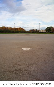 A baseball diamond from behind home plate with fall foliage beyond the outfield