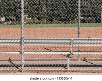 Baseball dugout bench. View behind the chain link fence. Infield and outfield in blurred background.