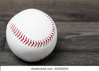 Baseball equipment: ball on a wood plank or bench background