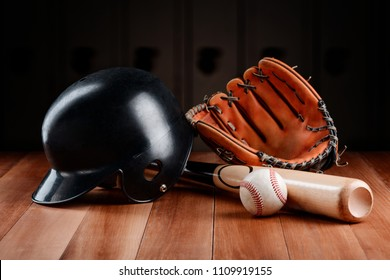 Baseball equipment and gear items on a wooden table. Catcher's helmet, glove, bat and ball.