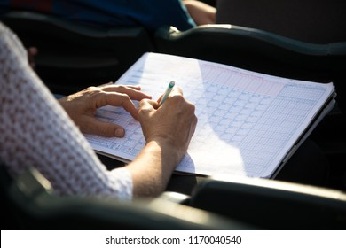 Baseball fan keeping score in a scorekeepers book, with space for text on the right