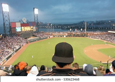Baseball fan watching night game in San Francisco. The fan is wearing a black baseball cap turned backwards and a black jacket with orange piping. Horizontal.