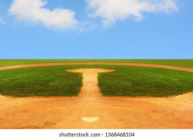 A Baseball field looking out to an endless horizon with a bright blue sky with fluffy white clouds