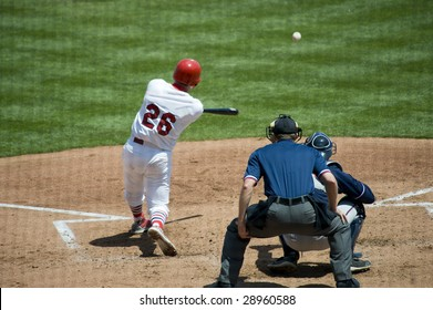 A baseball game with a batter, catcher and umpire on a beautiful sunny day