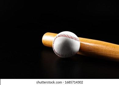Baseball game equipment on dark black background close up
