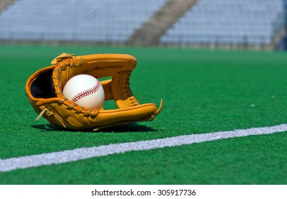 Baseball glove and ball laying in the green stadium field