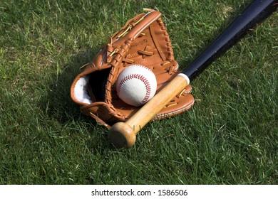 Baseball glove and bat against a grass background