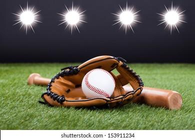 Baseball Glove With Baseball And Bat Lying On Green Grass