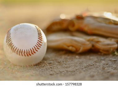 Baseball and Glove in Dirt