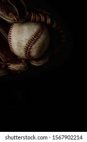 Baseball glove and baseball on black background