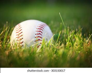 a baseball in a grass during sunset