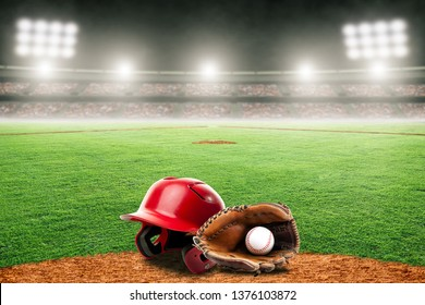 Baseball helmet, glove and ball on field at brightly lit outdoor stadium. Focus on foreground and shallow depth of field on background and copy space.