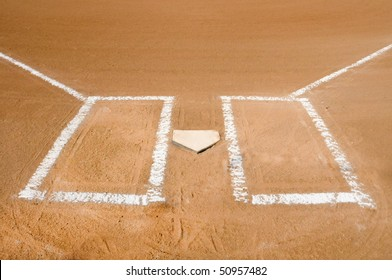 Baseball home plate with batter boxes freshly chalked.