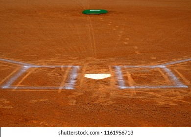 Baseball homeplate with batter box chalk lines in brown clay dirt