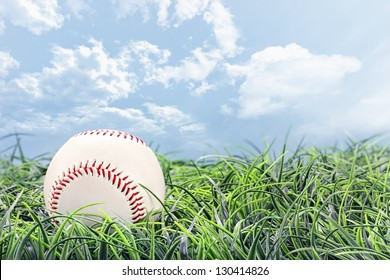 Baseball in lying in the grass on a beautiful summer day.
