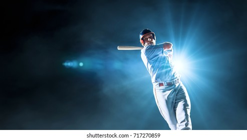 Baseball male player performs a dramatic play on the dark background. He wears unbranded sport clothes. The background is made in 3D.