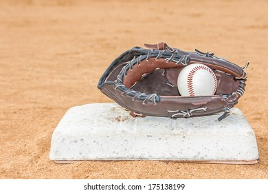 Baseball mitt and ball touching base in red sandy dirt infield. Ball inside glove. Low angle view, blurred background. room for text, copyspace. Horizontal photo.
