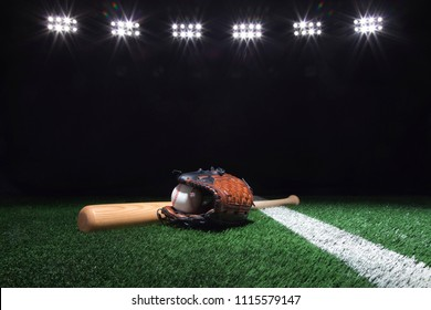 Baseball, mitt and bat on grass field with stripe under lights at night