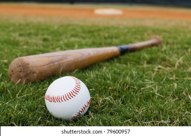 Baseball and old bat on field with base and outfield in background.