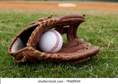 Baseball in old glove on field with base and outfield in background.