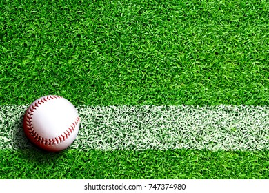 Baseball on field with white line marking and copy space. Line represents infield line or foul line.