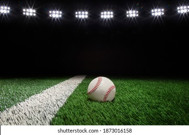 Baseball on a grass field with stripe and black background under lights