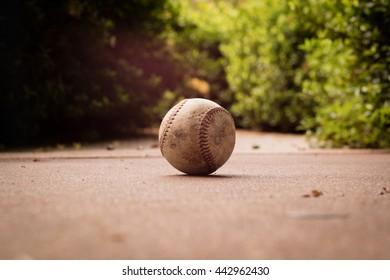 Baseball on the ground. Backlit.