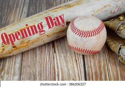 Baseball opening day on the first Sunday in April image of old baseball equipment including a worn ball and glove or mitt on a wooden background with Opening Day text added on bat. Copy space