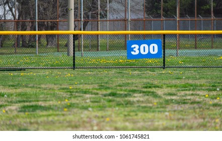 Baseball outfield 300 yard sign, grass and fence with trees in the background