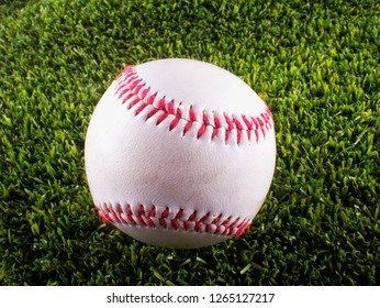 Baseball over synthetic green grass, close up