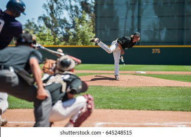 Baseball pitcher following through on pitch to right handed batter.