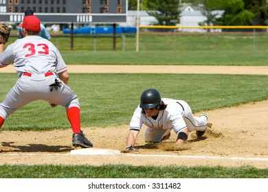 Baseball player dives back to first base as a pickoff attempt is made. Scoreboard in the background.