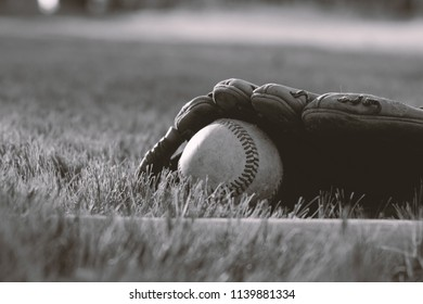Baseball player equipment in black and white lays in outfield with ball and glove.  American recreation sport season for old summer fun.